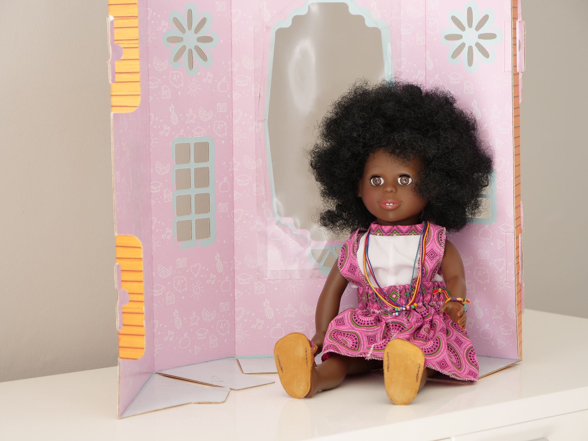 afro girl hunadi sitting by her doll house