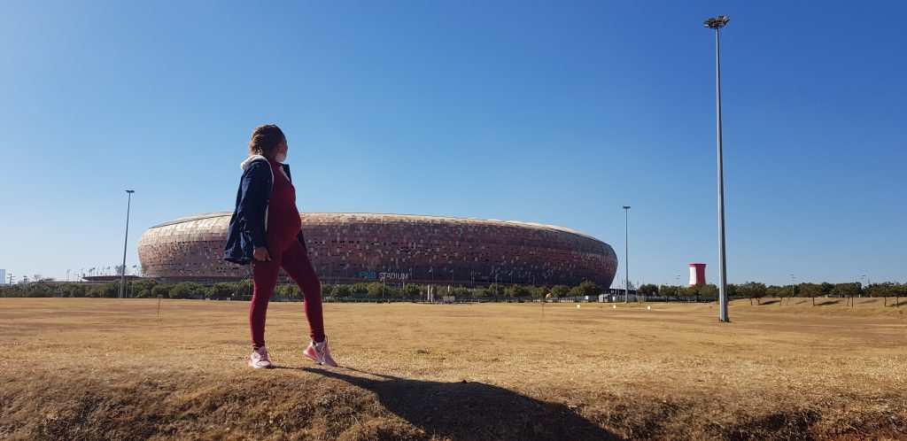 Pregnant woman looking back at FNB stadium also known as soccer city in Soweto