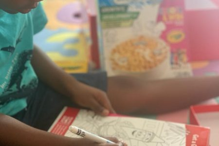 Child colouring in cereal box